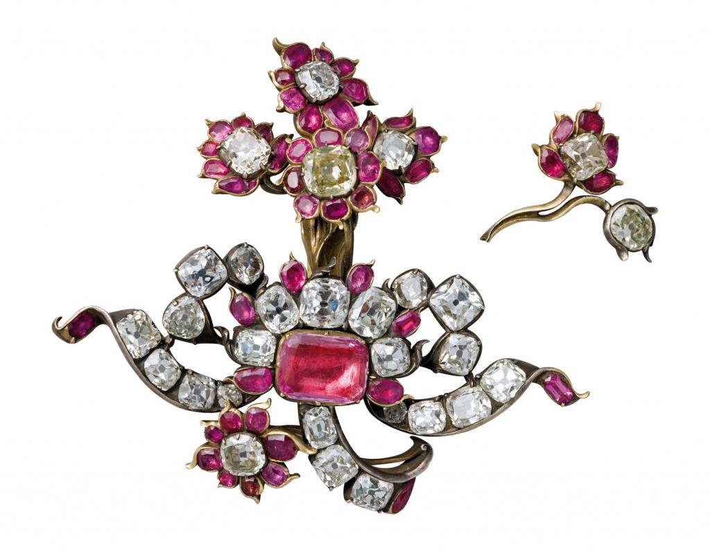 Aguja de oro y plata con diamantes, granates y un topacio rosa.