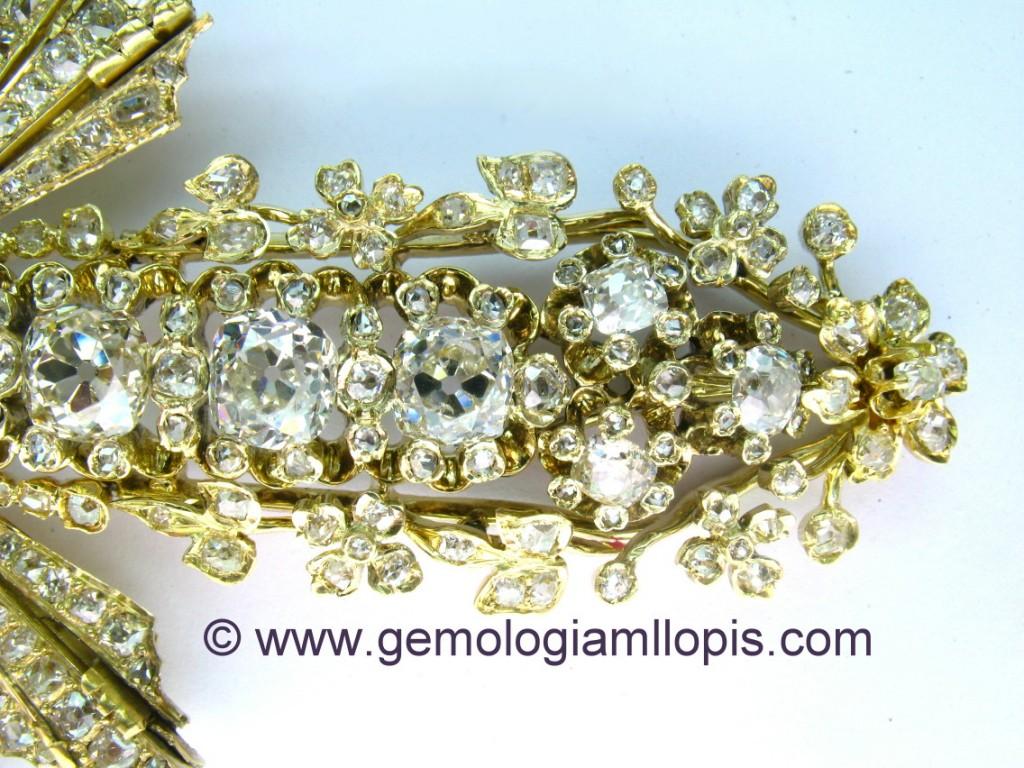 Detalle del pie de la cruz pectoral  de diseño floral con diamantes.