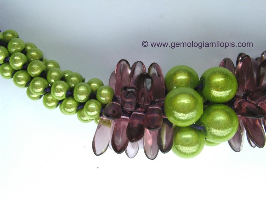 Centro de collar con bolas verdes de plástico y vidrios morados.