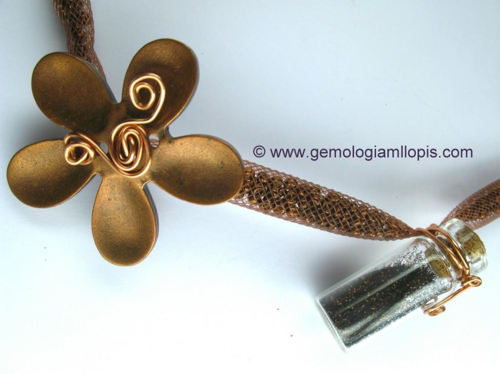 Centro de collar con flor de plástico, hilo dorado de aluminio, malla de plástico con pequeños donuts de vidrios.