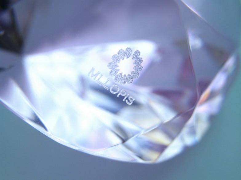 Ejemplo de grabado con láser de un logotipo  en un vidrio rosa decorativo.