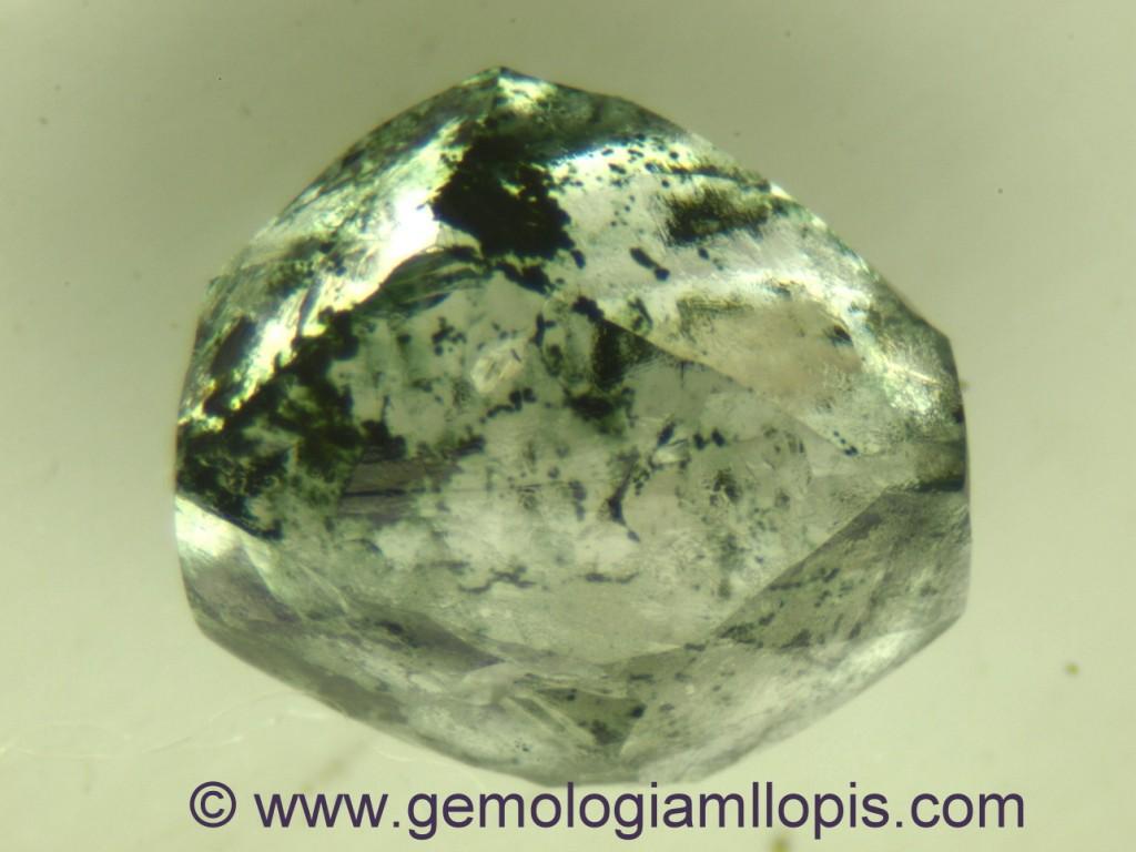 Bruto de diamante tratado por irradiación. Observar las manchas oscuras que vistas con lupa son verdosas