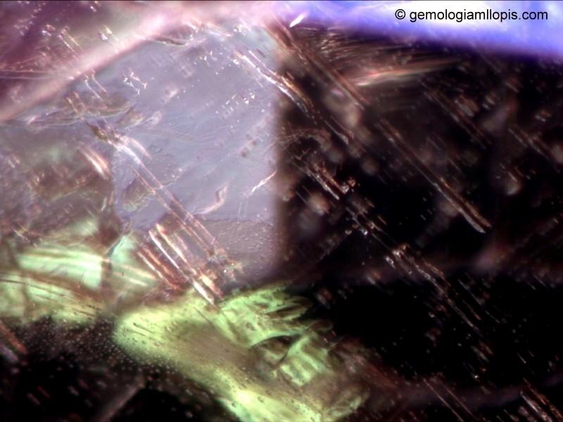 Desdoblamiento de las inclusiones por la elevada birrefringencia de la gema. Luz de campo oscurro, 60x.